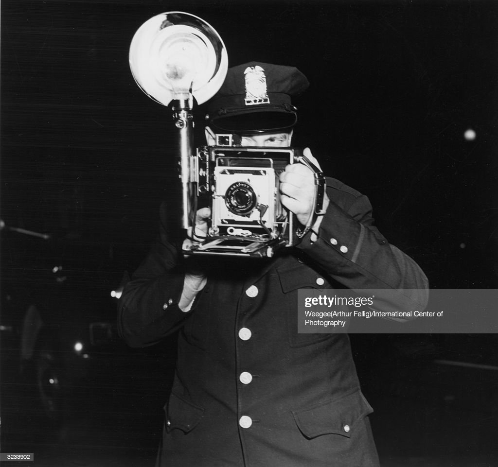 A policeman in Washington, DC, takes a photograph with the aid of a flashbulb. (Photo by Weegee(Arthur Fellig)/International Center of Photography/Getty Images)