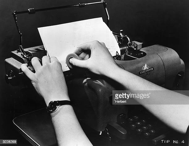 A secretary uses an eraser to fix a mistake on a page in her Underwood typewriter 1940s