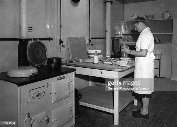A woman bakes in a kitchen containing an Aga stove