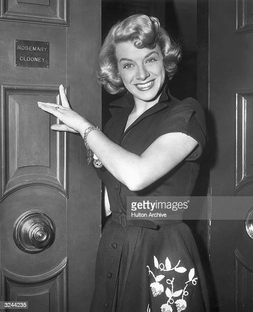 American actor and singer Rosemary Clooney points to her nameplate on the exterior of a door