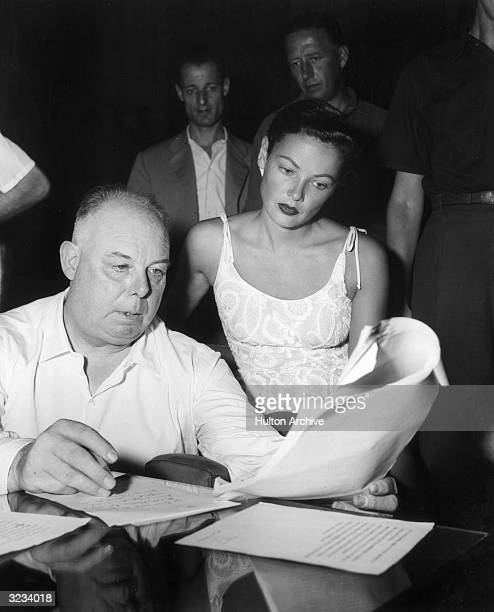 American actor Gene Tierney wearing a lace top sits next to French director Jean Renoir as they look over the preview of the program for the annual...