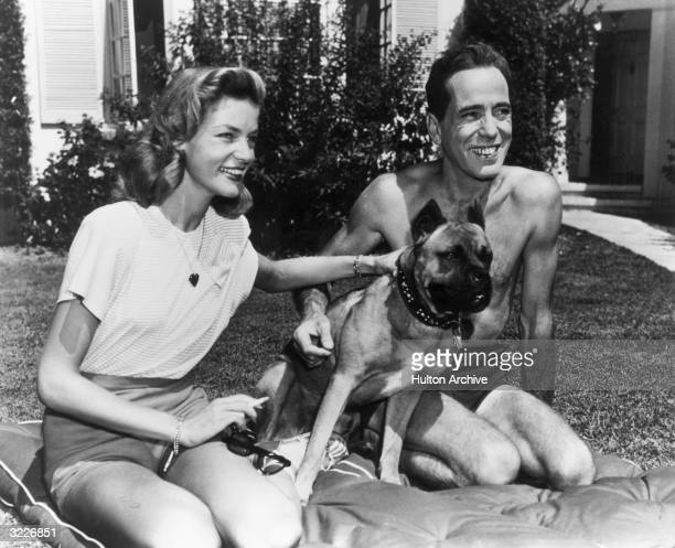 American actor Humphrey Bogart smiles as he kneels with his wife actor Lauren Bacall and their pet dog on a cushion on their front lawn Bogart wears...