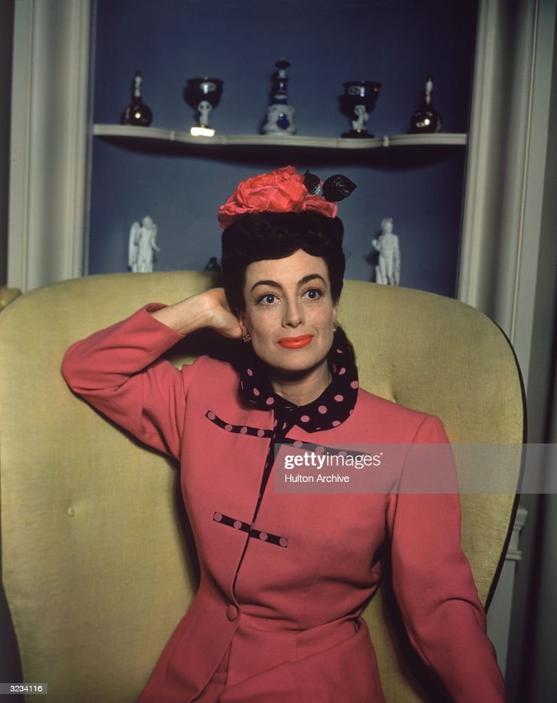 American actor Joan Crawford sits in a yellow chair with her hand behind her head She wears a hot pink dress suit with a polka dot collar and a...