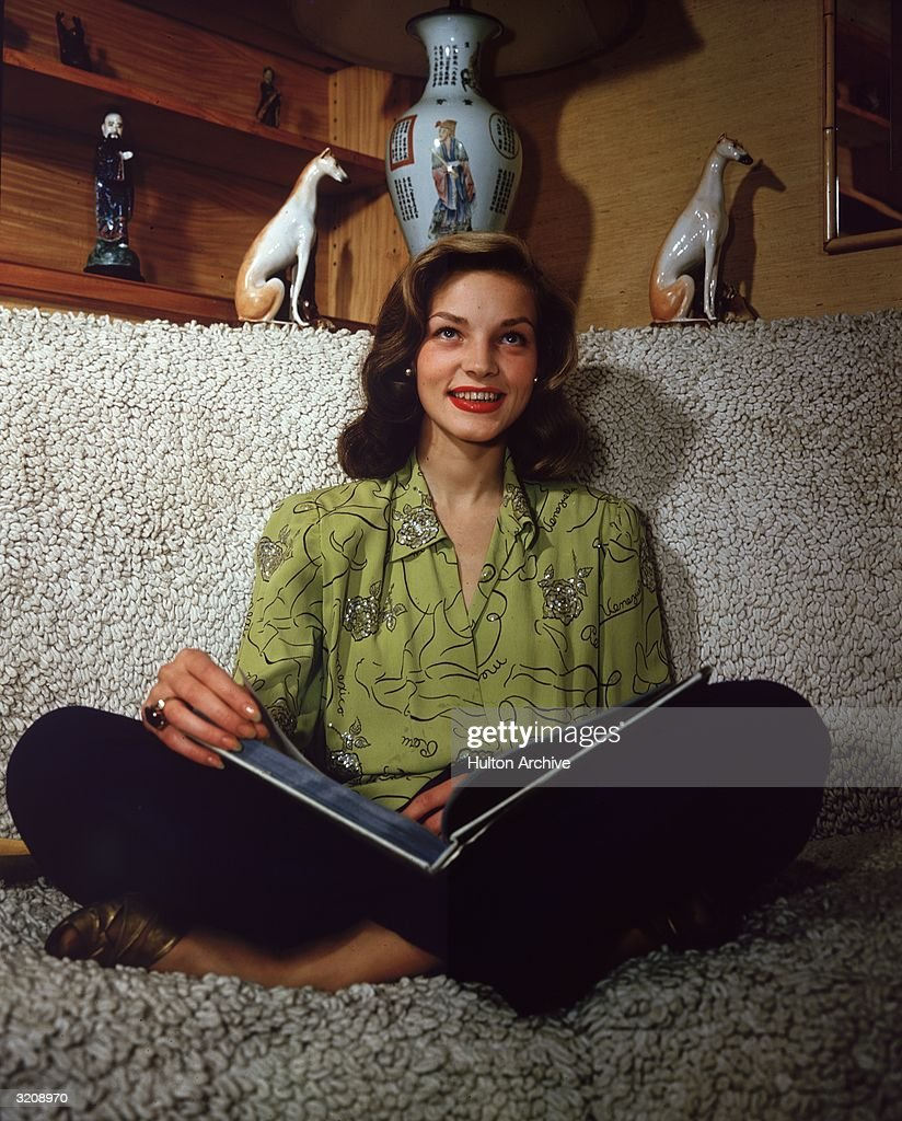 American actor Lauren Bacall smiling and sitting crosslegged on a sofa an open book in her lap
