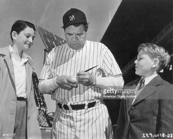 American baseball player Babe Ruth outfielder for the New York Yankees autographs a baseball for two young fans