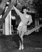 American film actress Joan Crawford posing in a garden in front of a tree and a children's slide