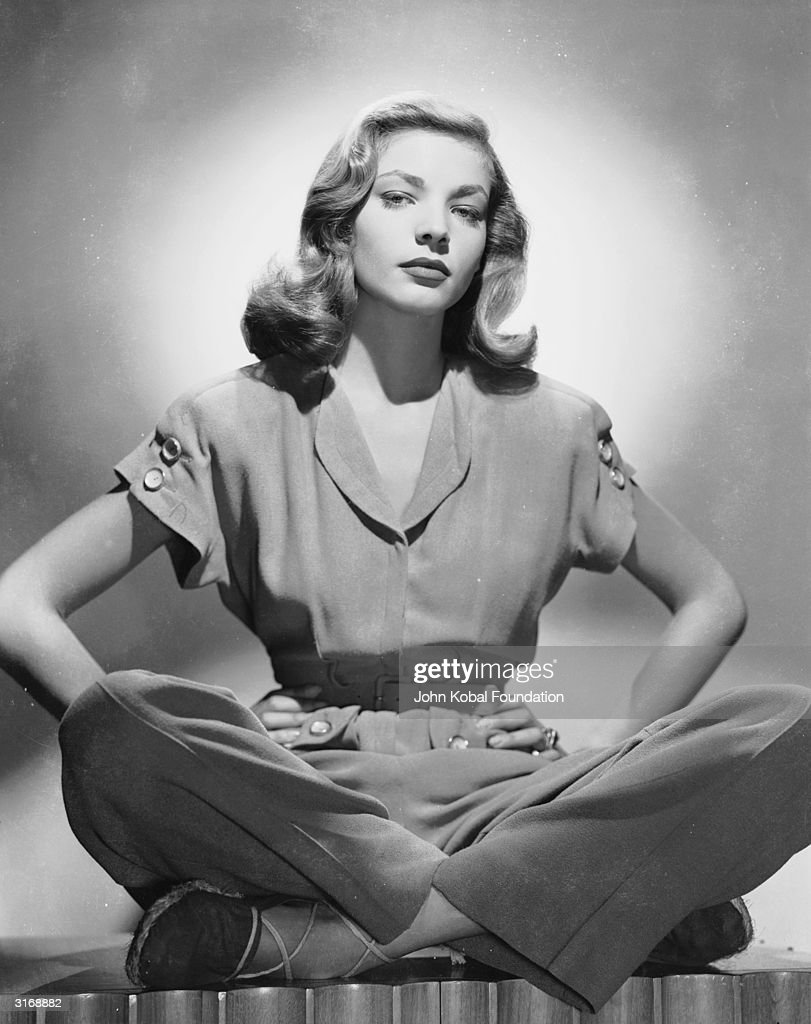 American screen star Lauren Bacall sitting crosslegged in a trouser suit with her hands on her hips