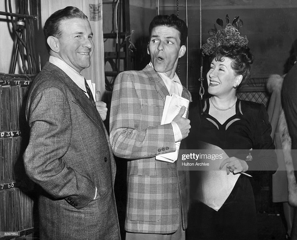 American singer and actor Frank Sinatra makes a face as he stands between married American actors and comedians George Burns and Gracie Allen on a...