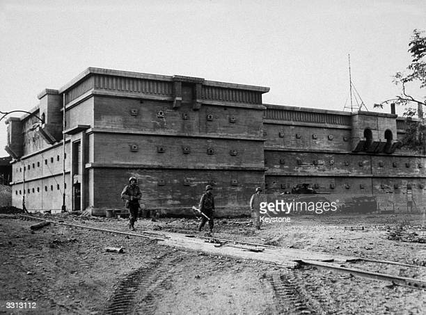 American troops seen in front of a vast air raid shelter capable of holding thousands of people in Aachen Germany