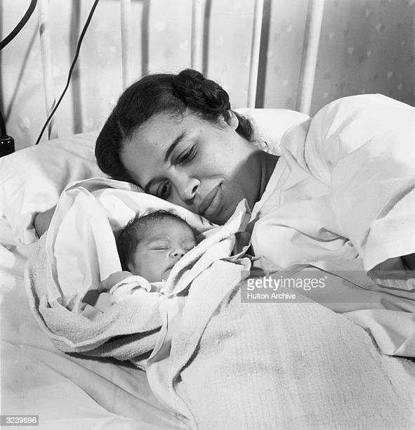 An AfricanAmerican mother lays in bed smiling with her newborn baby wrapped in a blanket beside her at Princeton Hospital Princeton New Jersey