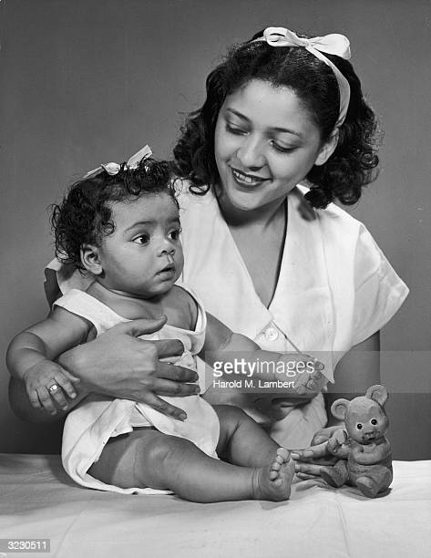 An AfricanAmerican mother smiles as she holds her infant daughter There is a toy bear on the counter They wear matching ribbons in their hair