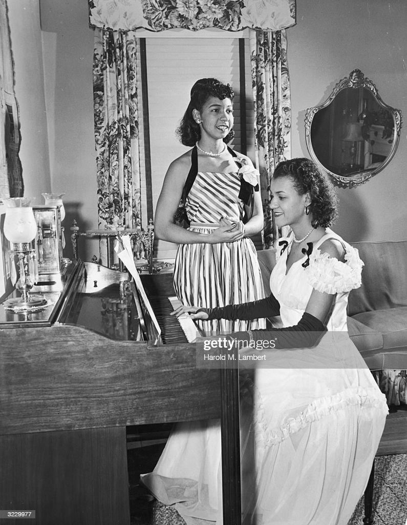 An AfricanAmerican woman plays the piano while another AfricanAmerican woman sings alongside her in a living room Both wear formal gowns