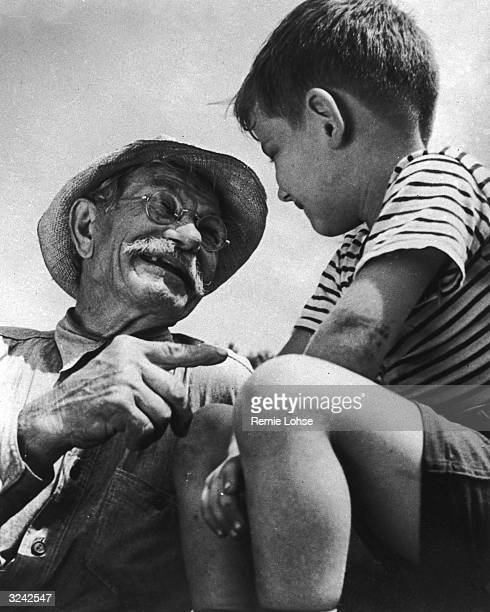 An elderly man wearing a straw hat points as he speaks with a young boy outdoors 1940s The boy wears a striped Tshirt