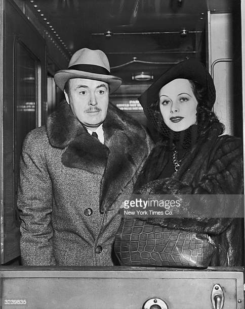 Austrianborn actor Hedy Lamarr with her second husband screenwriter Gene Markey stand inside a ship She wears a fur coat and her arm is resting on a...