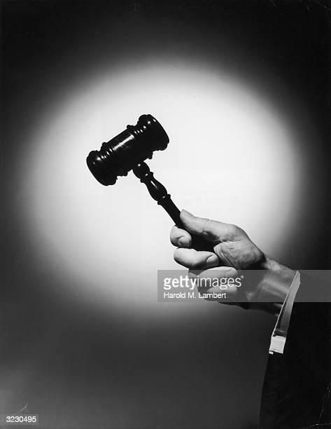 Closeup of a judge's hand holding a wooden gavel up in a spotlight