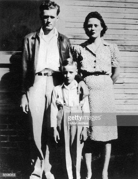 Elvis Presley standing between his parents outside of their home in Tupelo Mississippi