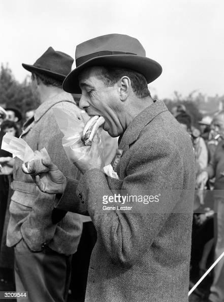 EXCLUSIVE Actor Humphrey Bogart eating a hot dog at the Santa Anita racetrack in Santa Anita California