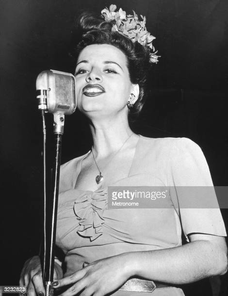 EXCLUSIVE American singer Kay Starr wearing an orchid in her hair and a heartshaped locket singing behind a microphone