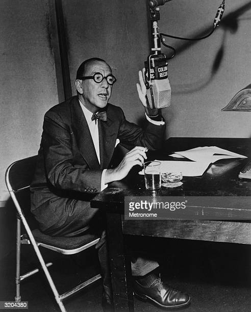 EXCLUSIVE British writer composer actor and director Noel Coward with a cigarette and water glass seated at a table and speaking into a hanging...