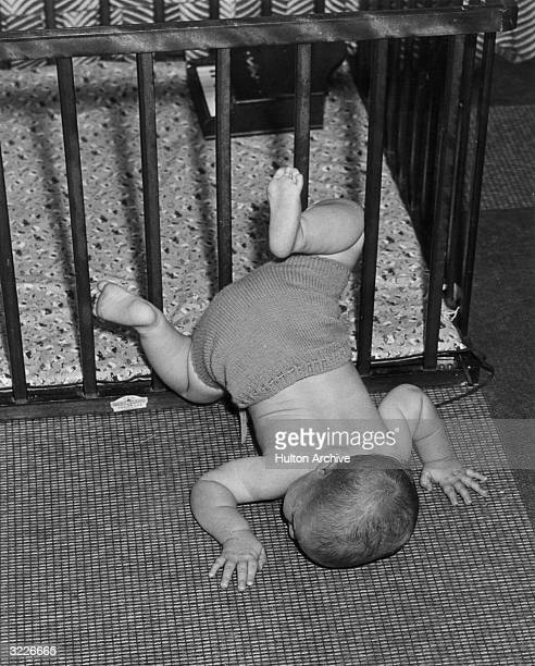 Fulllength image of a baby in wool shorts laying face down on a rug after falling out of its wooden crib