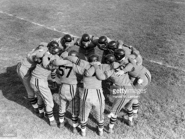 Fulllength image of a football team wearing uniforms and helmets huddling in a circle on the field during a football game 1940s