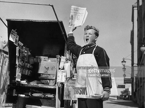 Fulllength image of a newsboy shouting beside a newsstand while holding a newspaper in the air and a bundle of 'The Evening Bulletin' newspapers...