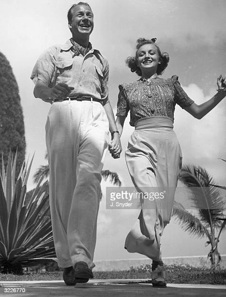 Fulllength low angle image of a man and woman smiling and holding hands as they walk down the street There are palm trees waving behind them