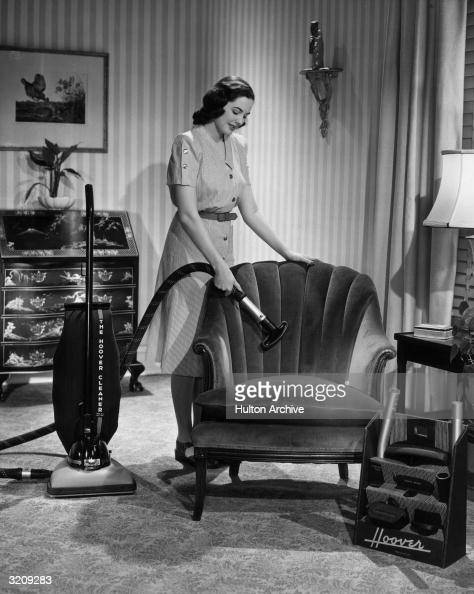 Fulllength portrait of a woman in a living room vacuuming a chair with a Hoover vacuum cleaner