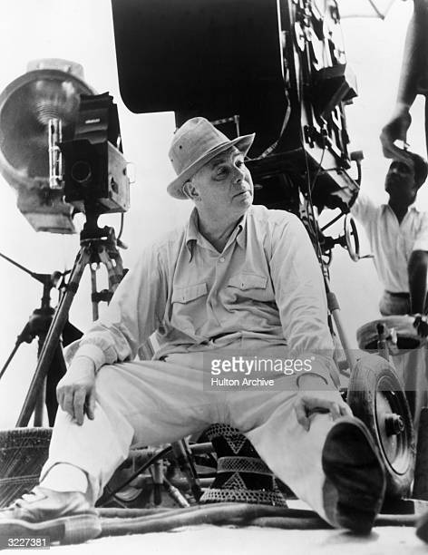 Fulllength portrait of French film director Jean Renoir sitting on a film set with his legs spread apart There is a camera behind him