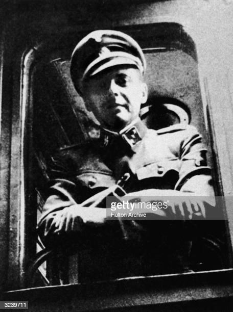 German Nazi doctor and war criminal Josef Mengele standing at a train window his SS uniform