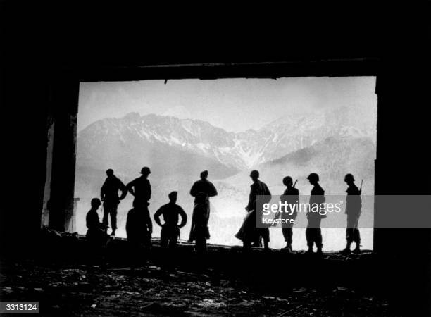 GIs stand at the ruins of the great living room window of Hitler's mountain retreat in Berchtesgaden the socalled Berghof