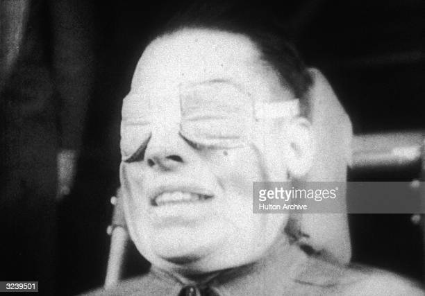 Headshot of a US military test subject undergoing Gforce testing while seated and wearing padded eye protection His face is distorted into a grin