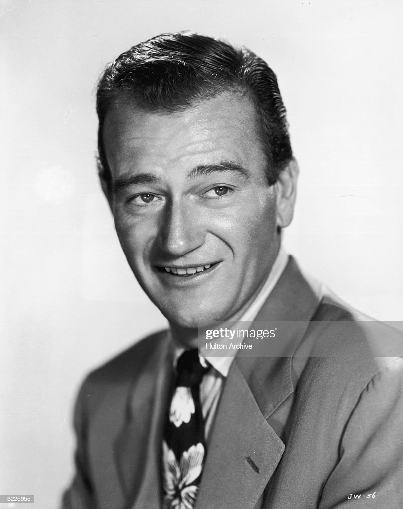 Headshot promotional portrait of American actor John Wayne, smiling and wearing a suit and a tie with flowers on it.
