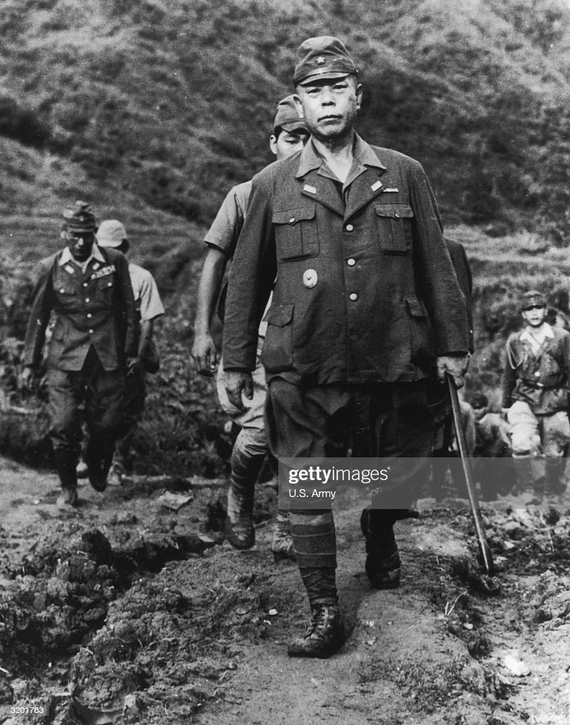 Japanese army general Tomoyuki Yamashita uses a cane while walking along a dirt road ahead of several soldiers. Yamashita was known as the 'Tiger of Malaya' for his leadership of the Japanese forces against the British troops in the Philippines.