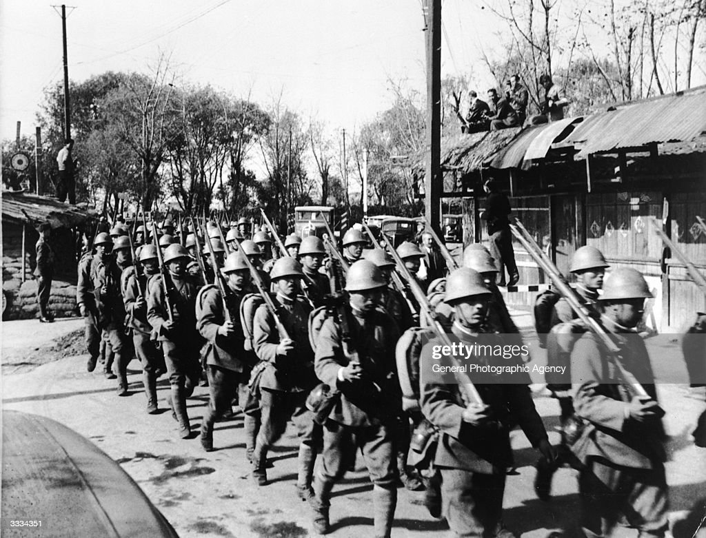 Japanese troops marching past a British post