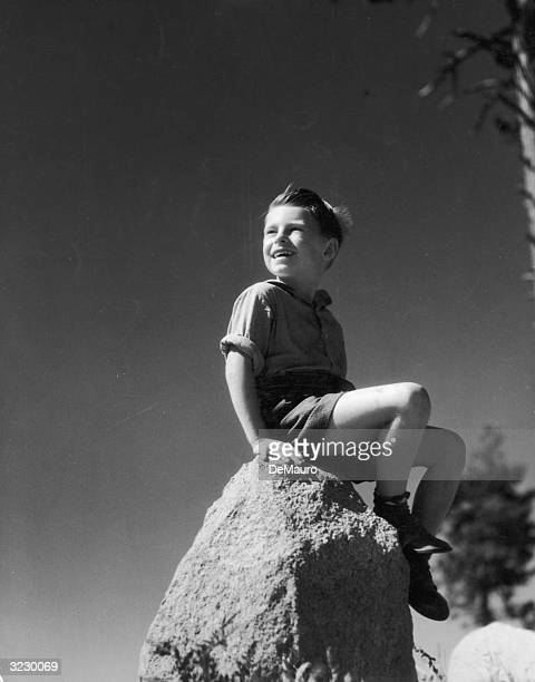 Low angle image of a young boy sitting outdoors on top of a large rock smiling with the wind blowing his hair 1940s He wears shorts with his shirt...