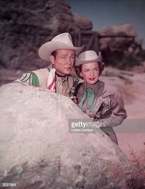 Married American actors and singers Dale Evans and Roy Rogers hold guns while standing behind a boulder in Western costumes in a film still