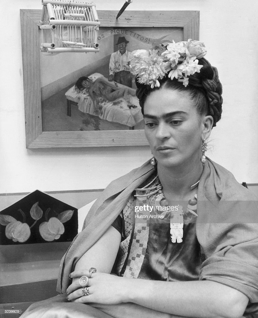 Mexican painter Frida Kahlo (1907 - 1954) sits with her arms folded, looking down, in front of one of her paintings and a wooden bird cage. She wears flowers in her hair and a wooden necklace.