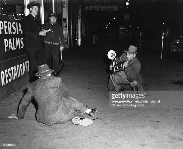 Polish born American photographer Weegee photographs at the scene of a crime Photo by Weegee/International Center of Photography/Getty Images