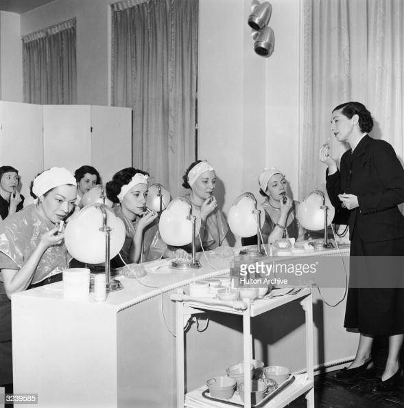 Polishborn cosmetics mogul Helena Rubinstein conducts a televised makeup class with a group of women seated in front of mirrors