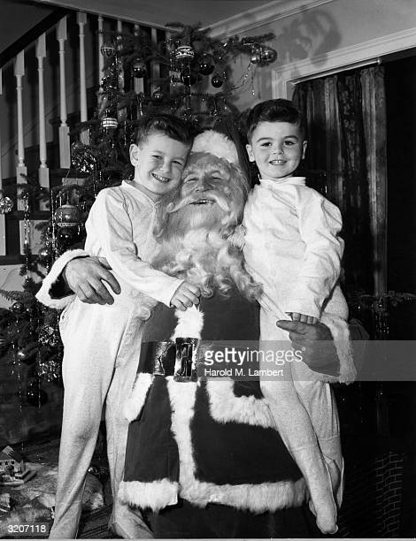 Portrait of a man dressed as Santa Claus smiling as he hugs two young boys wearing pajamas at his sides in front of a decorated Christmas tree