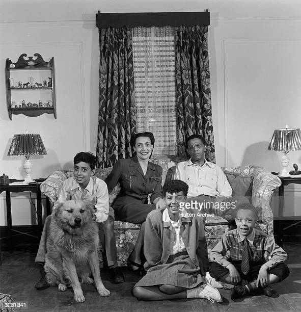 Portrait of a middle class AfricanAmerican family and their dog in their living room