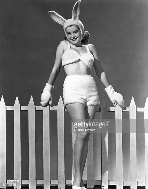 Portrait of American actor Barbara Bates leaning against a white picket fence in an Easter bunny costume consisting of a cap with rabbit ears gloves...