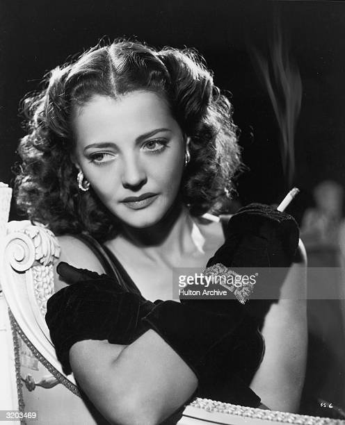 Portrait of American actor Sylvia Sidney sitting with her arms folded across her chest while holding a burning cigarette She wears long black gloves...