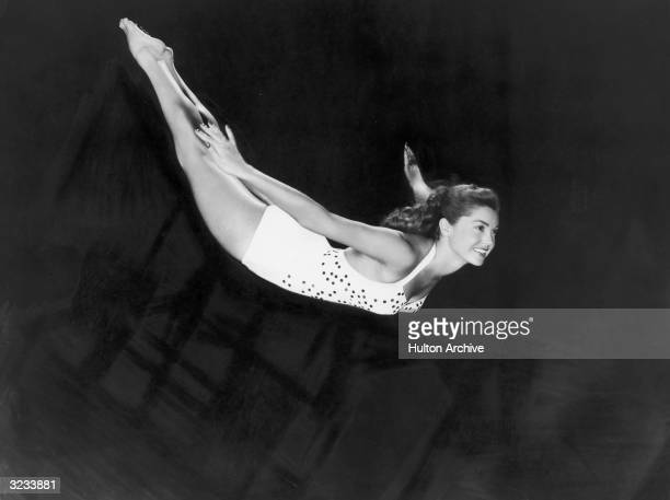 Portrait of aquatic American actor and swimmer Esther Williams diving through the air in a onepiece swimsuit