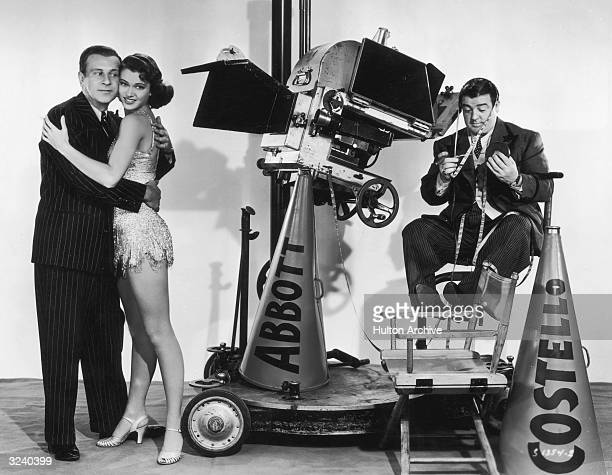 Promotional portrait of American comedy team Bud Abbott and Lou Costello clowning on a film set with a young woman a movie camera a tape measure and...