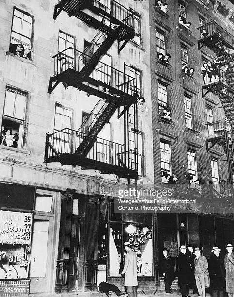 Residents hang out of their windows to watch the proceedings after a street murder Photo by Weegee/International Center of Photography/Getty Images