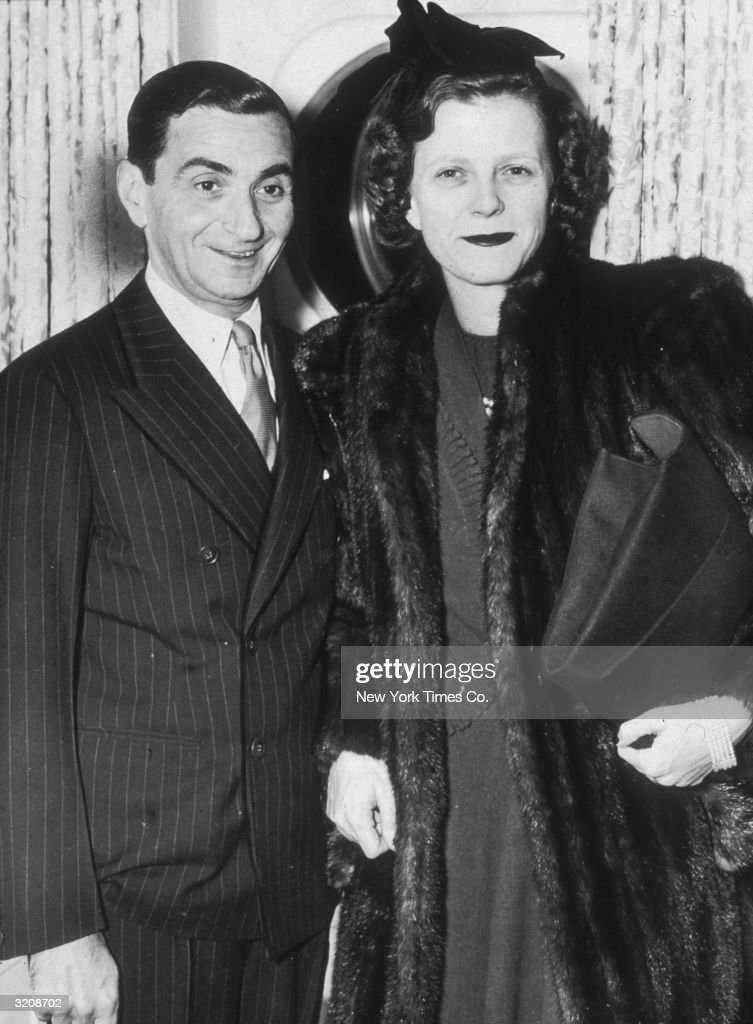 Russian-born composer <a gi-track='captionPersonalityLinkClicked' href=/galleries/search?phrase=Irving+Berlin&family=editorial&specificpeople=208654 ng-click='$event.stopPropagation()'>Irving Berlin</a> (Israel Baline, 1888 - 1989) smiles with his wife Ellin Mackay, standing on board the oceanliner America. Mackay wears a fur coat and holds her purse.