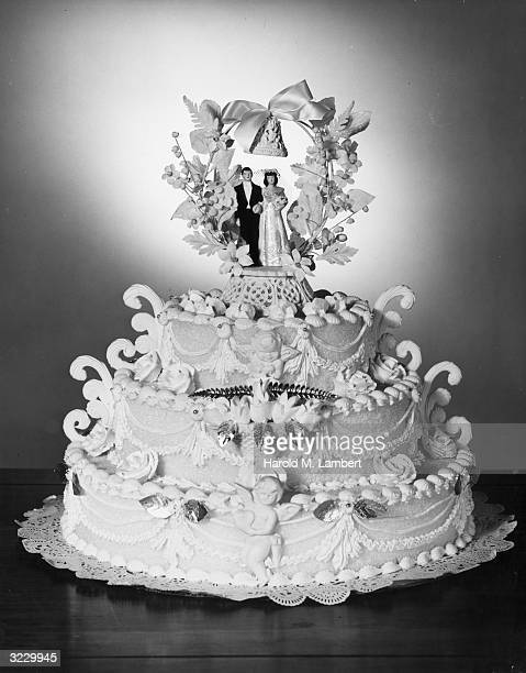 Stilllife of a threetiered wedding cake decorated with figurines of a bride and groom standing beneath a wreath on the top layer