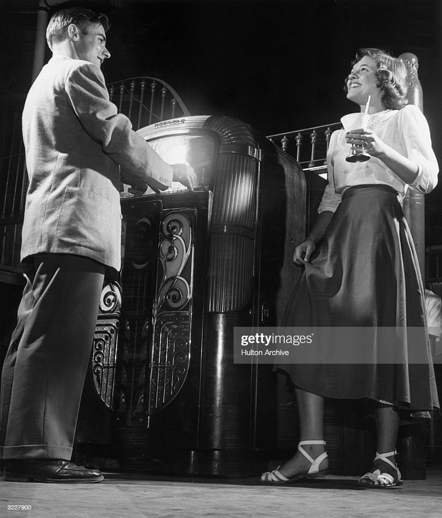 Students Beverly Hough and George Kressan listen to music on the juke box inside a university malt shop.